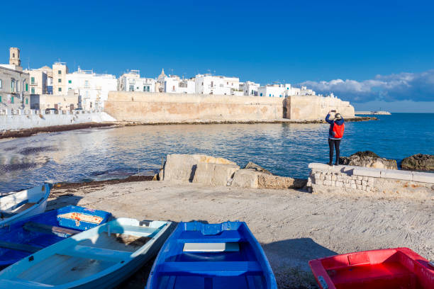Young tourist girl take a photo with smartphone with skyline of Monopoli in the background.