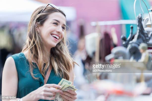Young tourist holds money ready for purchase in an outdoor street shop