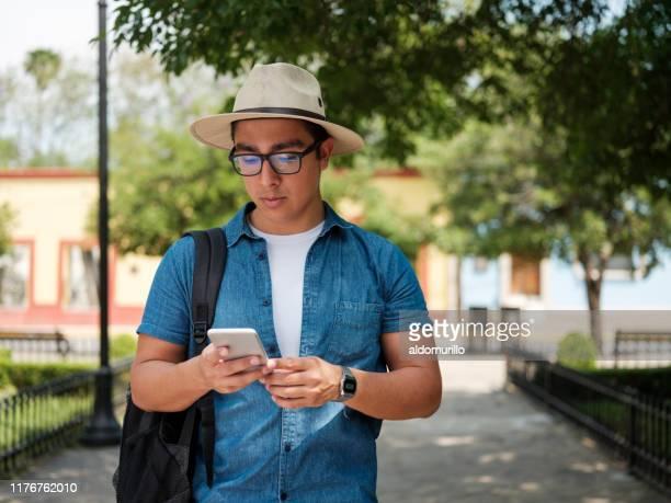 jeune touriste regardant son téléphone - plan moyen angle de prise de vue photos et images de collection