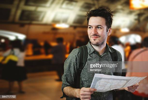 Young tourist man in Paris metro station looking at map