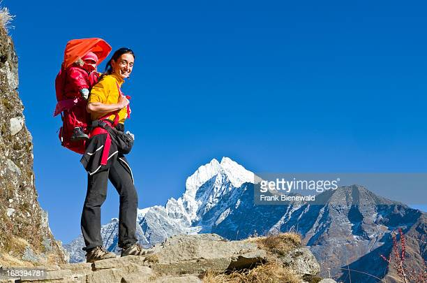 A young tourist mother carrying her little child in a child carrier rucksack on her back trekking above Namche Bazar the base for trekking and...