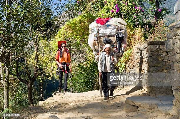A young tourist mother carrying her little child in a child carrier rucksack on her back walking beside a Nepali porter with big load She and her...