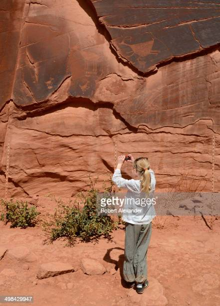 Young tourist photographs ancient Anasazi Native American petroglyphs during a tour of Monument Valley Navajo Tribal Park in southeastern Utah....