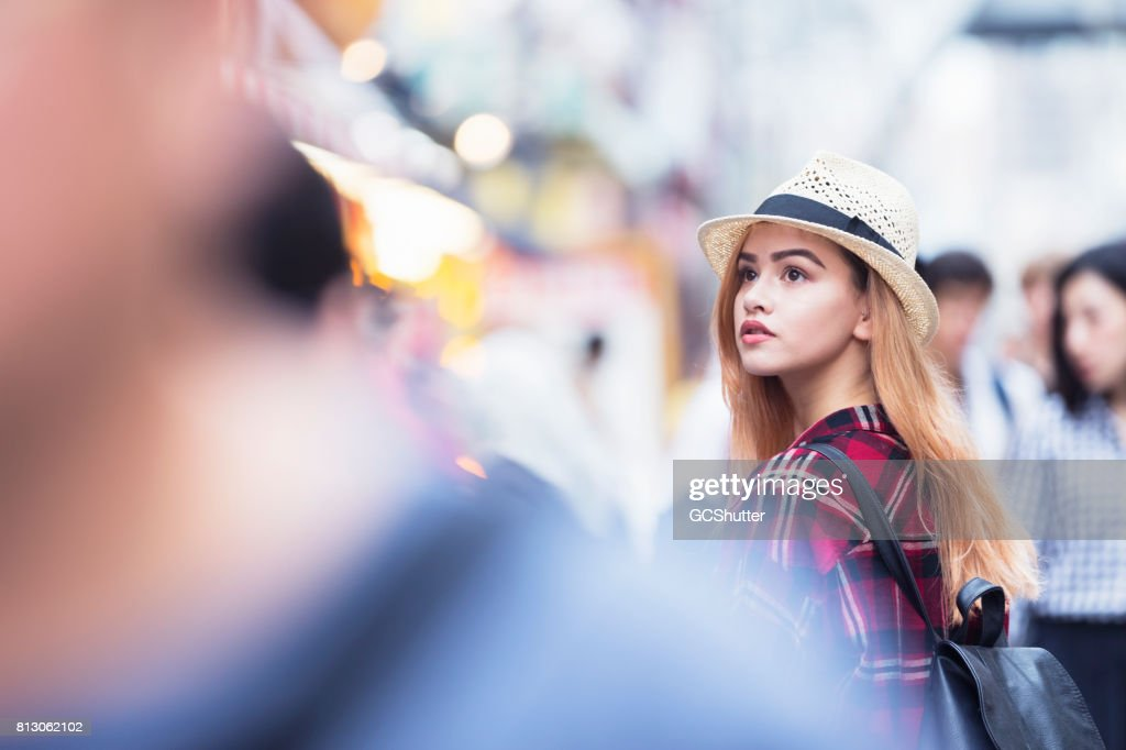 Young tourist roaming the famous streets of Shinsekai among large crowds of pedestrians : Stock Photo