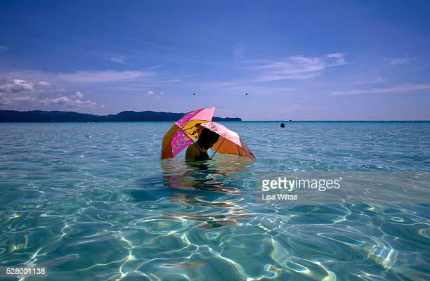 A young tourist shields herself from the sun with a colourful umbrella in the South China sea on White Sand beach in Boracay Visayas The Philippines...
