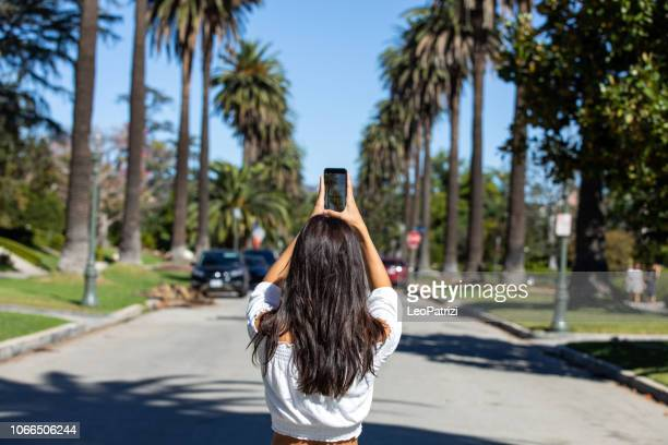Young tourist taking picture of famous places in Los Angeles, USA