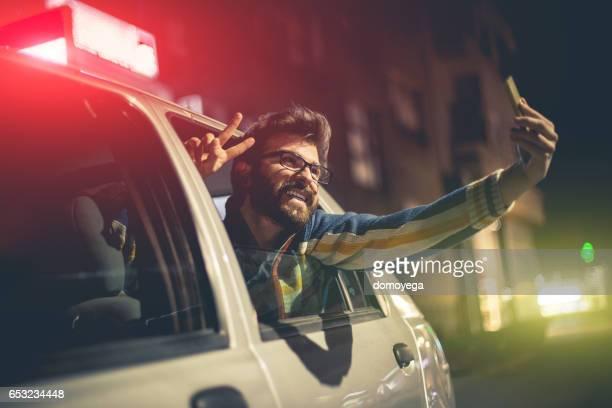 Jeune touriste prenant selfie dans le véhicule de taxi