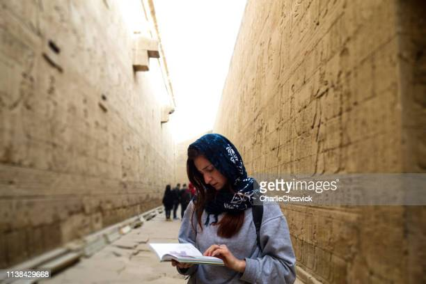 young tourist traveller reading guidebook in temple of edfu - egyptian god stock pictures, royalty-free photos & images