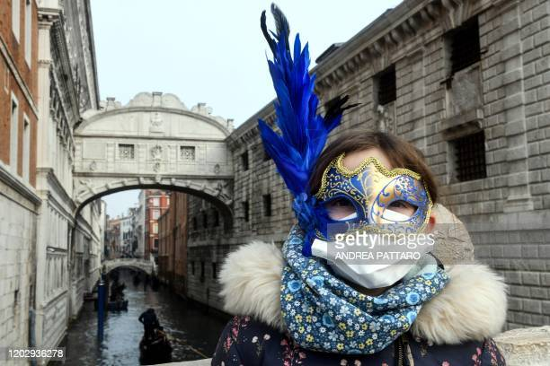 TOPSHOT A young tourist wearing a protective facemask and a Carnival mask visits the streets of Venice on February 24 2020 during the usual period of...