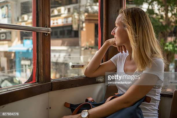 Young tourist woman on double decker cable car-Hong Kong