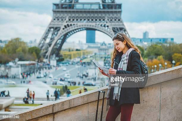 Jeune touriste femme lecture de plan de ville de Paris avec Tour Eiffel