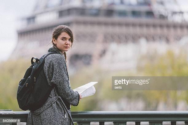 若い女性の読書パリ観光市内地図アゲインストツアーエッフェル