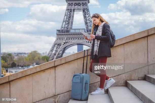 jovem turista mulher lendo mapa da cidade de paris passeio eiffel contra - frança - fotografias e filmes do acervo