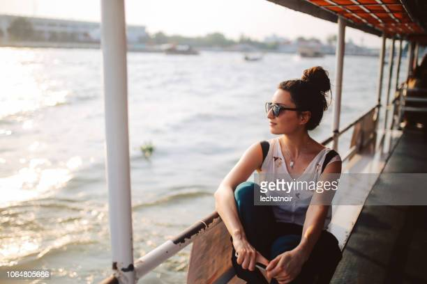 young tourist woman riding on the bangkok ferry boat - travel foto e immagini stock