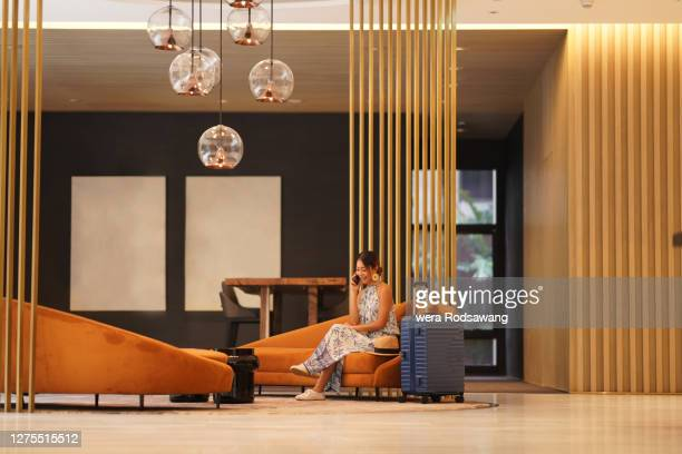 young tourist woman sitting on sofa at hotel lobby lounge using phone to talking and smiling - hotel stock pictures, royalty-free photos & images