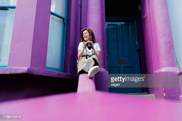 young tourist woman sitting on the color walls - purple stock pictures, royalty-free photos & images