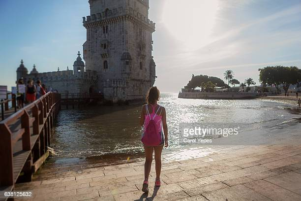 young tourist  woman standing in front of Belem Tower.Rear view