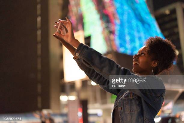 mulher jovem turista tirando fotos na avenida paulista, são paulo, brasil - mobile - fotografias e filmes do acervo
