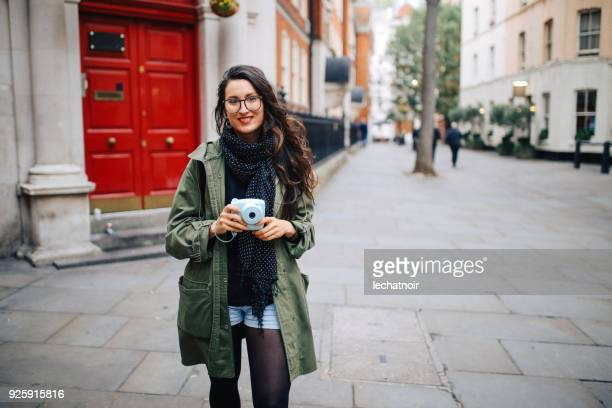 Young tourist woman walking on the streets of London holding her vintage film camera