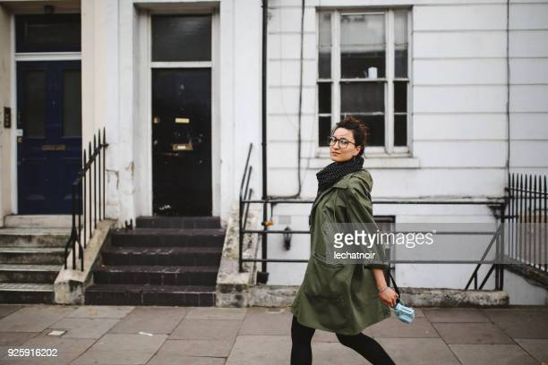 young tourist woman walking on the streets of london holding her vintage film camera - parka coat stock photos and pictures