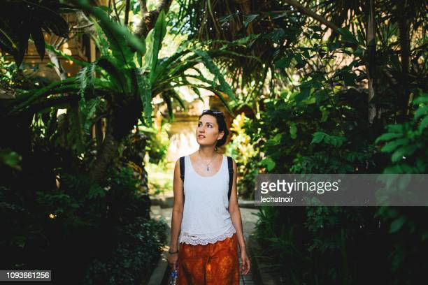 young tourist woman walking through the tropical forest in bali, indonesia - balinese culture stock pictures, royalty-free photos & images