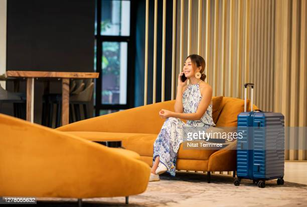 young tourist women on phone call by sitting on sofa at hotel lounge , entrance hall. - travel stock pictures, royalty-free photos & images