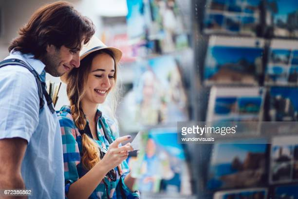 Young tourists buying postcards from souvenir shop