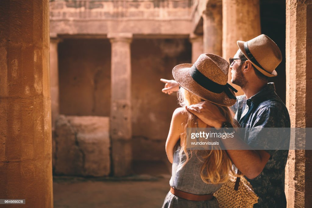 Young tourists couple doing sightseeing at ancient archaeological site : Stock Photo