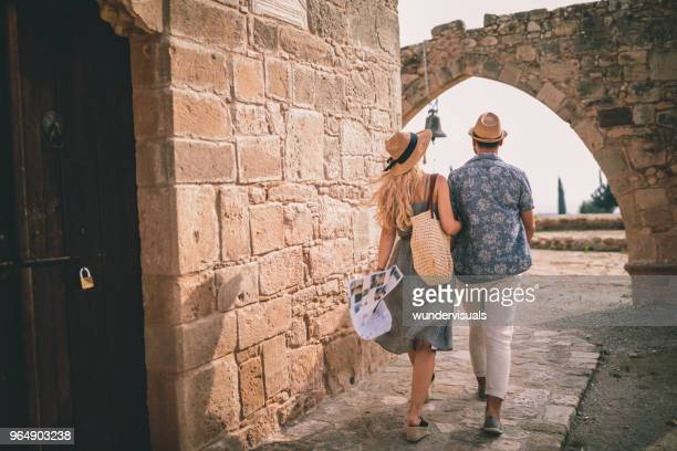 young tourists couple doing sightseeing at stonebuilt monument in europe - villaggio foto e immagini stock