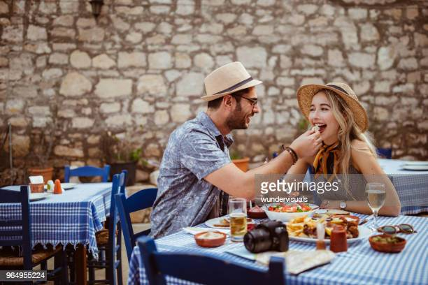 Young tourists couple eating meze at traditional Greek restaurant