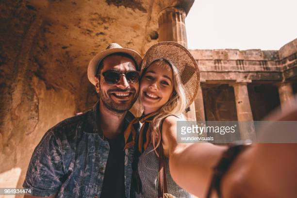 young tourists couple taking selfies at ancient monument in italy - turista foto e immagini stock