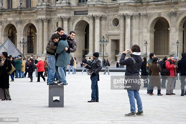 Young tourists having fun trying to balance on posing plinth outside the Louvre Museum Central Paris France