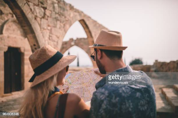 Young tourists reading map at old Mediterranean stonebuilt village