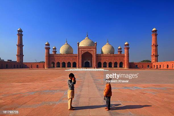 CONTENT] A young tourists taking photograph of his family member The Badshahi Mosque or the Royal Mosque in Lahore commissioned by the sixth Mughal...