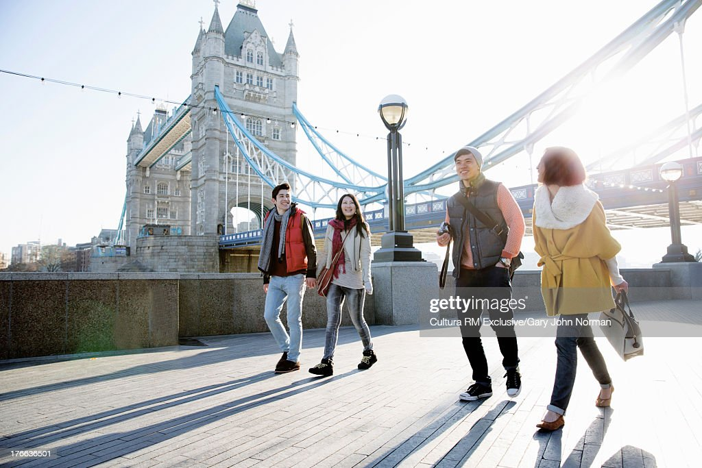 Young tourists walking past Tower Bridge, London, England : Stock Photo