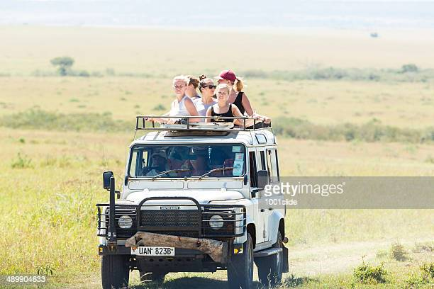 Young tourists watching wild life with safari car
