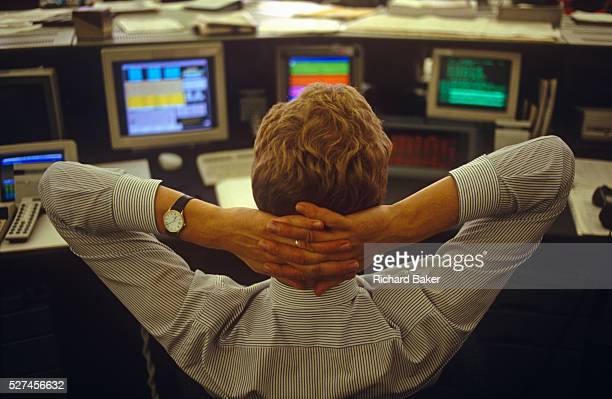 A young trader in currencies leans back in his chair on the currency trading floor of Barclays Bank in the City of London England UK Easing back...