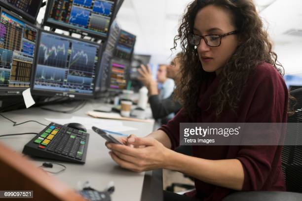 young trader using mobile phone - trading floor stock pictures, royalty-free photos & images