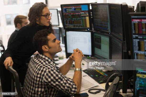 Young traders analyzing computer data