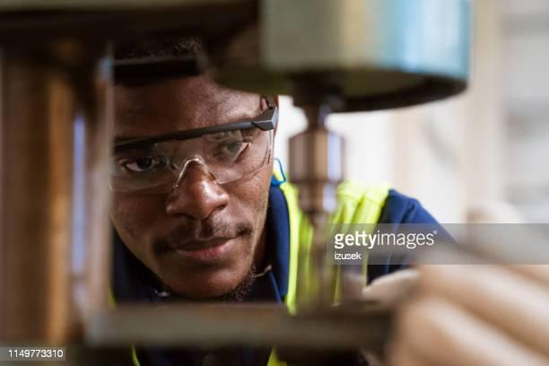 estagiário novo usando a máquina do garfo na fábrica - metalúrgico - fotografias e filmes do acervo