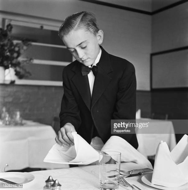 Young trainee waiter folds a white linen napkin at a dining table as part of his course at Westminster Technical School of Cookery for Boys in London...