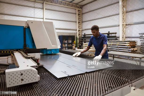 young trainee working on puller machine in factory - sheet metal stock pictures, royalty-free photos & images
