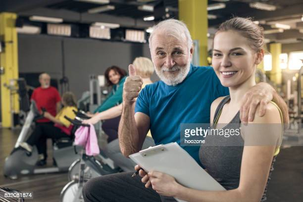 Young trainer with senior client at gym