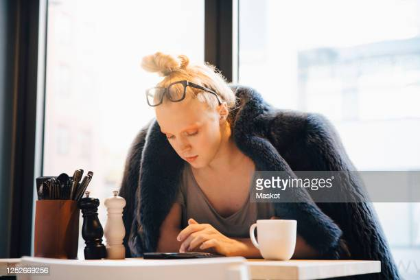 young transgender customer using smart phone while sitting at table in cafe - transgender stock pictures, royalty-free photos & images