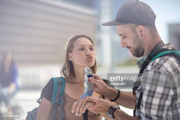 Young traveler couple applying sun cream