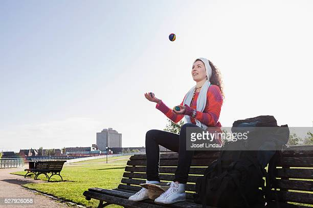 Young traveler juggling balls for money