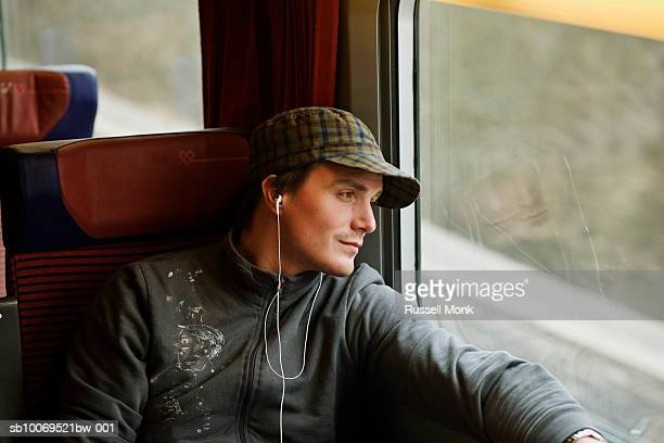 Young traveler listening to mp3 player, sitting on train and looking out of window