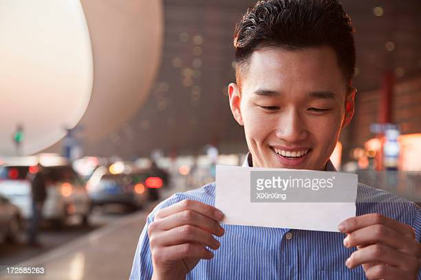 Young traveler looking at ticket at airport