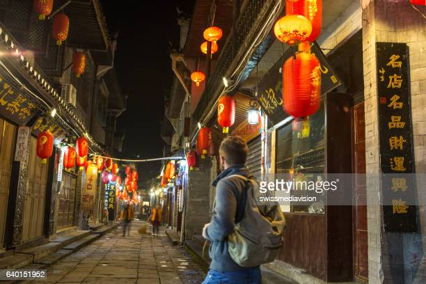 Young traveler man in alley of ancient village, China