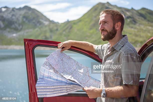 Junger Reisender auf road trip lesen Karte